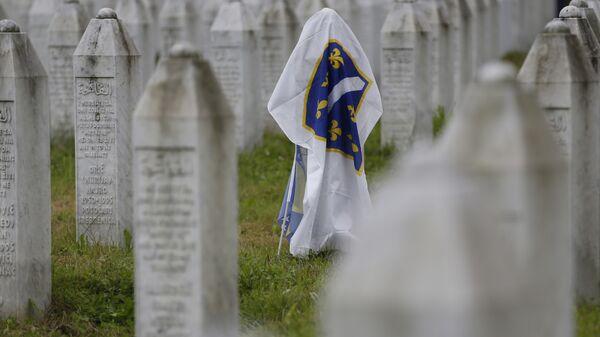 Бывший Боснийский флаг на одном из надгробий в мемориальном центре Потокари около Сребреницы