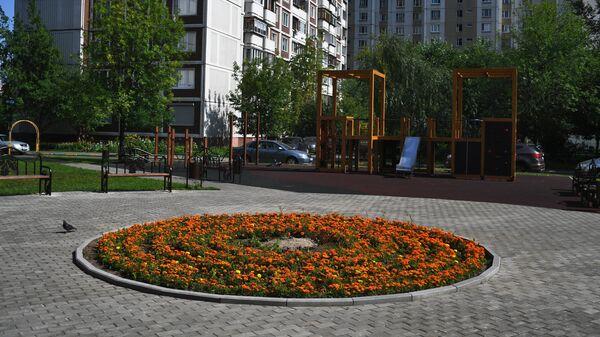Детская игровая площадка и цветочная клумба во дворе дома в Москве