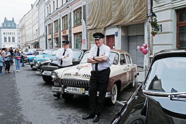 Участники ГУМ-авторалли Gorkyclassic - 2018 у автомобиля «Волга» ГАЗ-21 перед стартом гонки у ГУМа в Москве