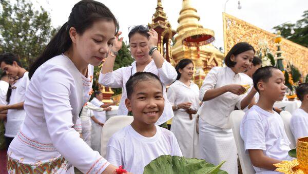 Мальчики из спасенной из таиландской пещеры детской футбольной команды Дикие вепри в буддийском храме в провинции Чианг Рай во время религиозной церемонии посвящения в монахи. Архивное фото