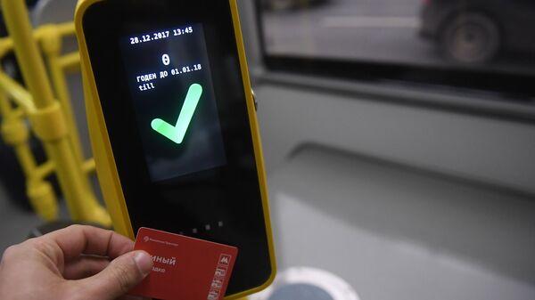 Пассажир прикладывает билет к валидатору в автобусе в Москве