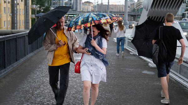 Прохожие на Крымском мосту во время дождя в Москве