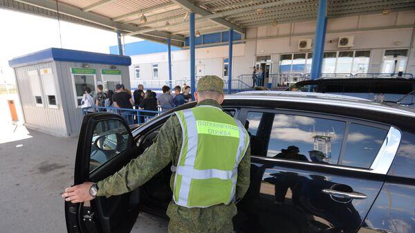 Сотрудник пограничной службы во время осмотра автомобиля на пограничном контрольно-пропускном пункте Бугристое российско-казахстанской границы