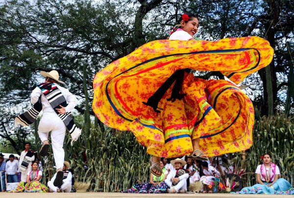 Танцоры на ежегодном фестивале La Guelaguetza в штате Оахака в Мексике.