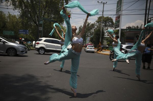 Балерины танцуют во время красного сигнала светофора в Мехико.