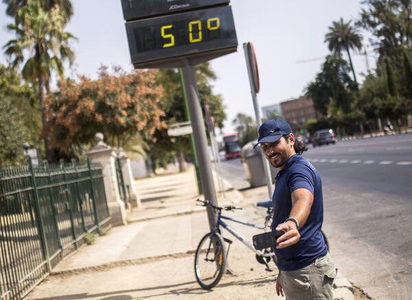 Мужчина фотографируется у электронного табло, которое показывает температуру +50 градусов по Цельсию на улицах города Севилья в Испании