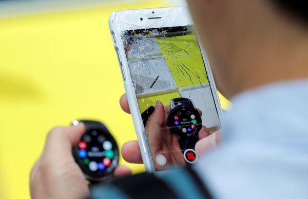 Посетитель фотографирует на iPhone часы Samsung Galaxy Watch на презентации Galaxy Unpacked в Нью-Йорке