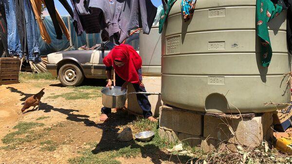Женщина набирает воду в палаточном лагере для сирийских беженцев. Архивное фото