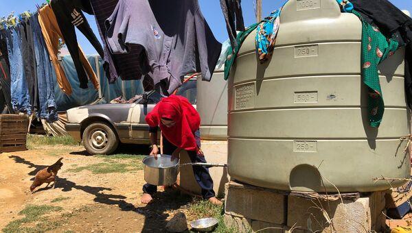 Женщина набирает воду в палаточном лагере для сирийских беженцев в центральном Бекаа в поселении Каб Эльяс. 11 августа 2018