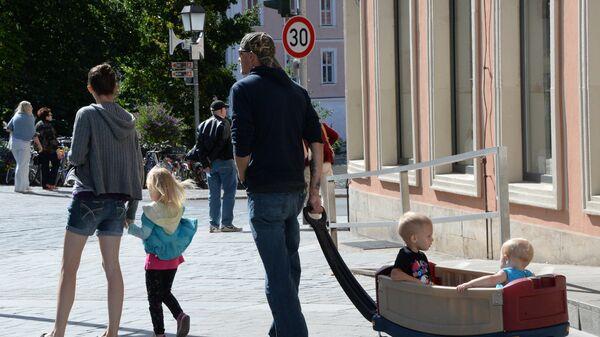 Семья с детьми гуляет на одной из улиц Бамберга, Германия