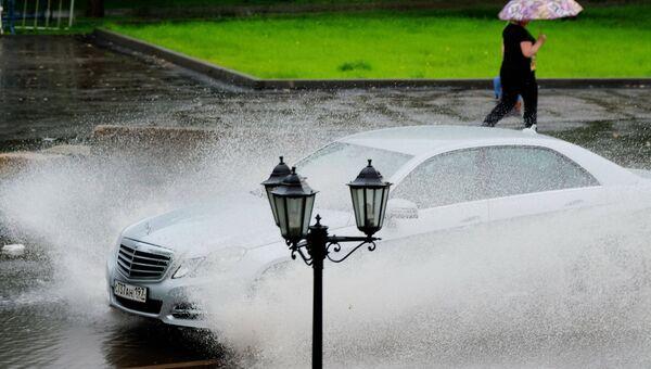 Автомобиль едет по улице во время дождя. Архивное фото