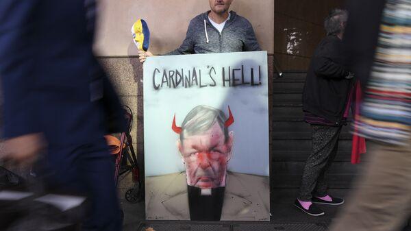 Протестующий с плакатом у здания суда в Мельбурне, где рассматривается дело в отношении кардинала Джорджа Пелла. 1 мая 2018