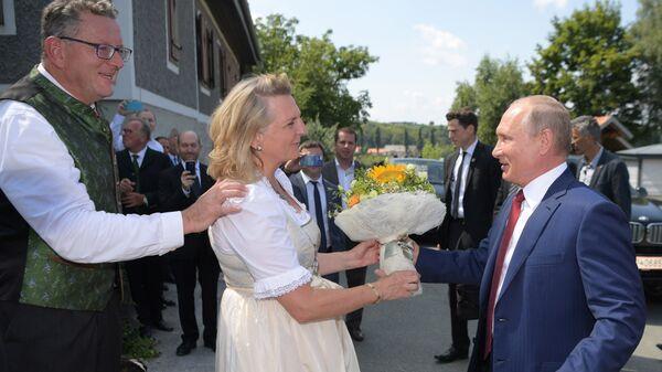 Президент РФ Владимир Путин дарит цветы министру иностранных дел Австрии Карин Кнайсль на ее свадьбе с финансистом Вольфгангом Майлингером