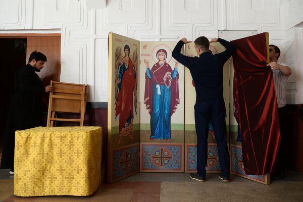 Участники духовно-просветительской миссии, корабля-церкви Святой апостол Андрей Первозванный устанавливают иконы в Доме культуры в селе Битки Новосибирской области
