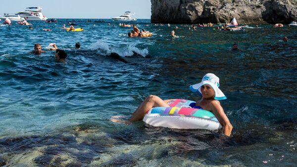Отдыхающие во время соревнований спортсменов на Международном Кубке мира по клифф-дайвингу в Симеизе