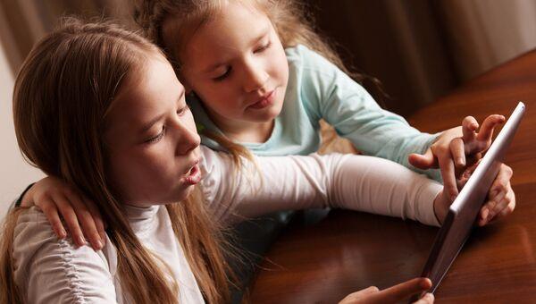Подростки сидят за столом с планшетом