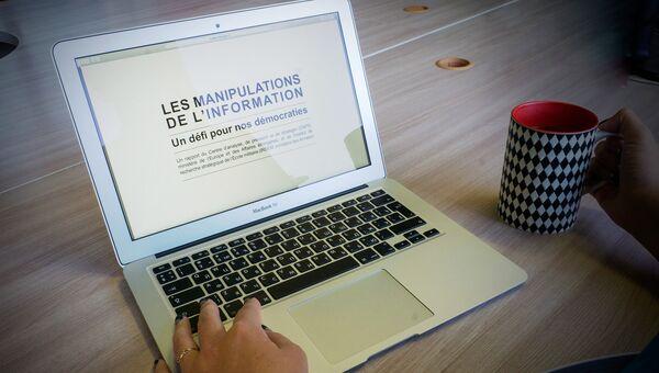 Девушка читает доклад, подготовленный Центром анализа, прогнозирования и стратегии (CAPS) при МИДе Франции и Институтом стратегических исследований (IRSEM) при Минобороны Франции