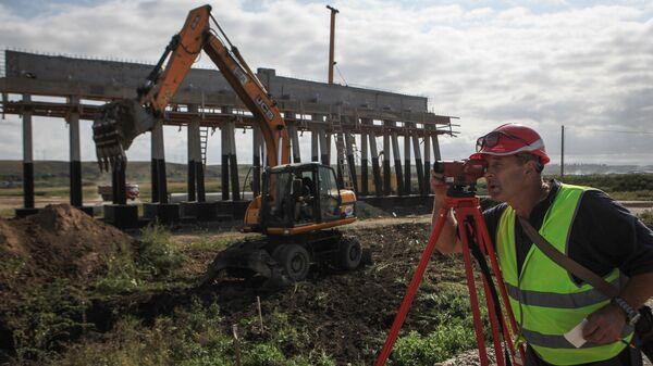 Рабочий на строительстве участка федеральной трассы Р-217 Кавказ в объезд озера Тамбукан протяженностью 15 километров в Кабардино-Балкарии