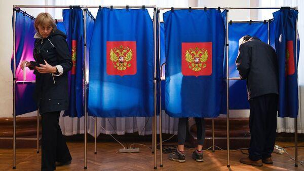 Избиратели в день голосования на избирательном участке. Архивное фото