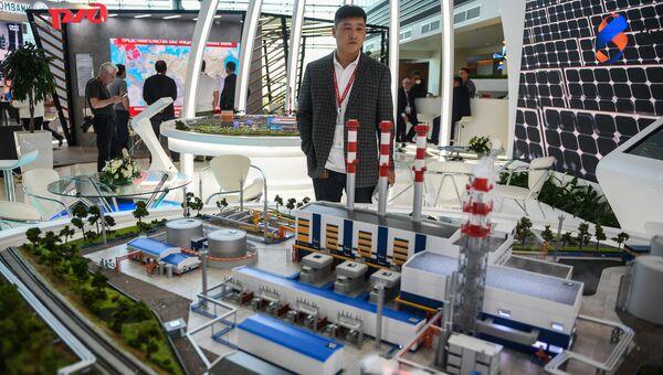 Посетитель осматривает макет ТЭЦ «Восточная» на стенде российской энергетической компании ПАО РусГидро