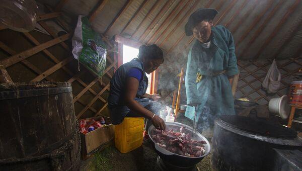 Монгольская женщина готовит еду в юрте
