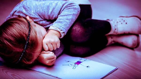 Маленькая девочка плачет на полу