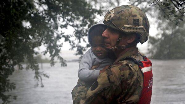 Сотрудник спасательного отряда Национальной гвардии эвакуирует ребенка