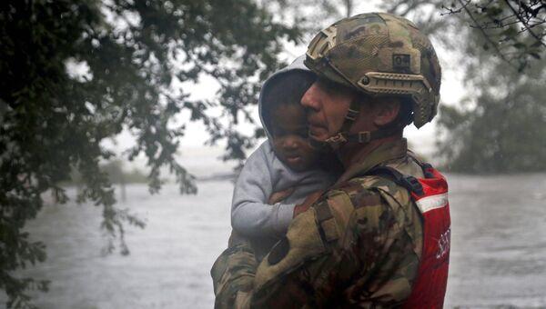 Сотрудник спасательного отряда Национальной гвардии эвакуирует ребенка во время наводнения, вызванного ураганом Флоренс, в Нью-Берне, Северная Каролина. 14 сентября 2018