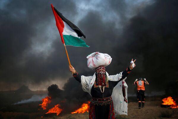Женщина с флагом Палестины на акции протеста возле границы с Израилем
