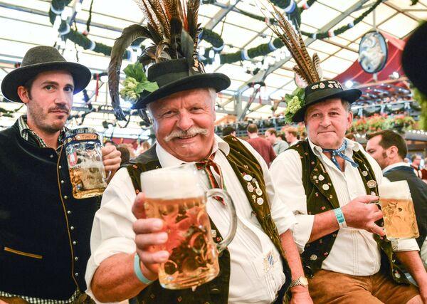 Посетители с пивом на открытии традиционного пивного фестиваля Октоберфест в Мюнхене