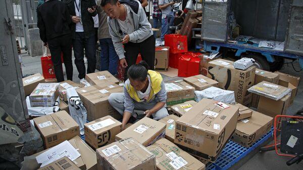 Сотрудники службы доставки сортируют посылки в Пекине