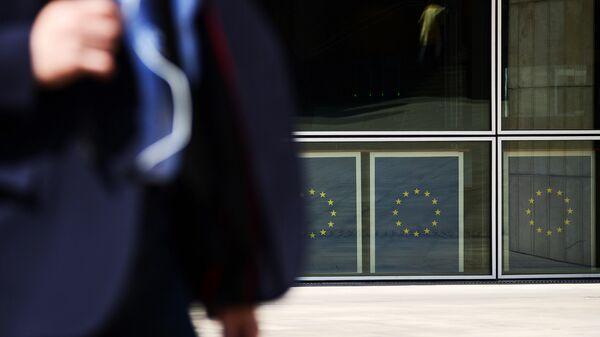 Мужчина на фоне флагов ЕС в Брюсселе