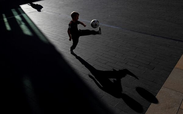 Мальчик играет в футбол возле Королевского фестивального зала в Лондоне