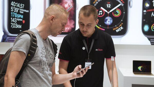 Мужчина рассматривает телефон iPhone XS Max в магазине re:Store торгово-развлекательного центра «Галерея» в Санкт-Петербурге