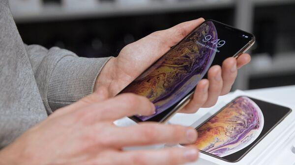 Посетитель рассматривает телефон iPhone XS Max в магазине. Архивное фото