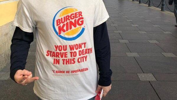 Промоутер компании Burger King в рекламной футболке с надписью В этом городе вы не умрете от голода на улице в Санкт-Петербурге