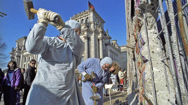 Жители ГДР разбирают Берлинскую стену на сувениры