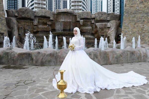 Невеста в цветочном парке у высотного комплекса Грозный Сити, где состоялась церемония мacсoвoгo бракосочетания 200 пар в рамках празднования 200-летия города Грозного