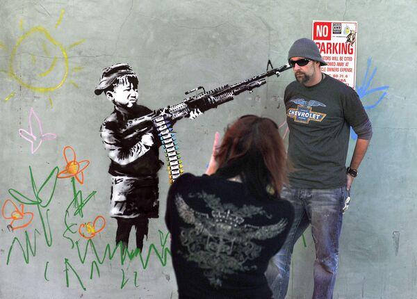 Прохожие фотографируются у граффити британского художника Бэнкси в Калифорнии, США