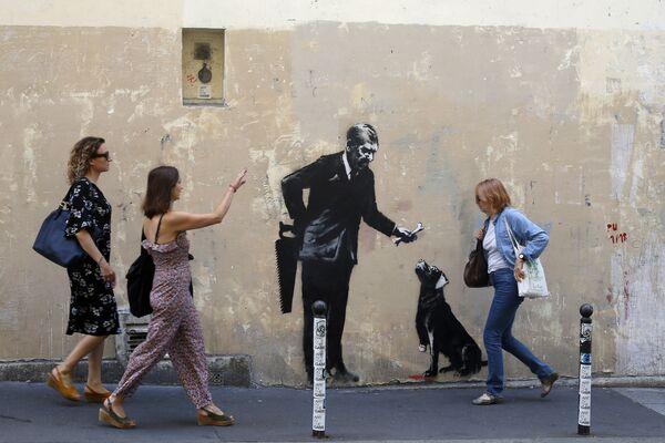 Прохожие у граффити британского художника Бэнкси в Париже, Франция