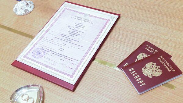 Кольца новобрачных, свидетельство о браке и паспорта молодоженов. Архивное фото