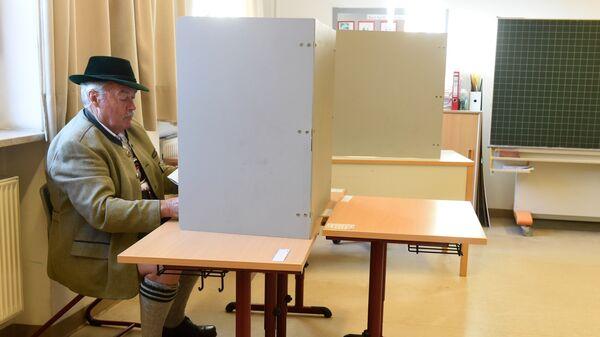 Мужчина в традиционной баварской одежде заполняет бюллетень для голосования на избирательном участке в Нойкирхене, Германия