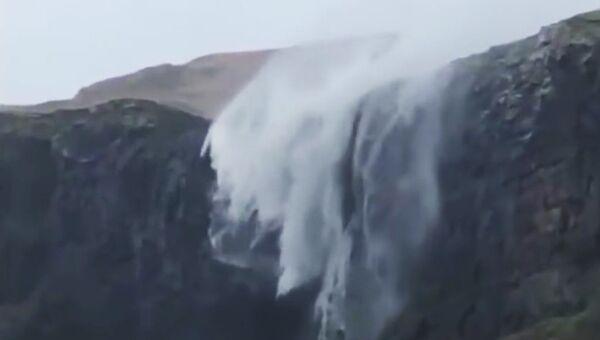 Кадр из видео, на котором ветер останавливает водопад во время шторма на пляже Талискер