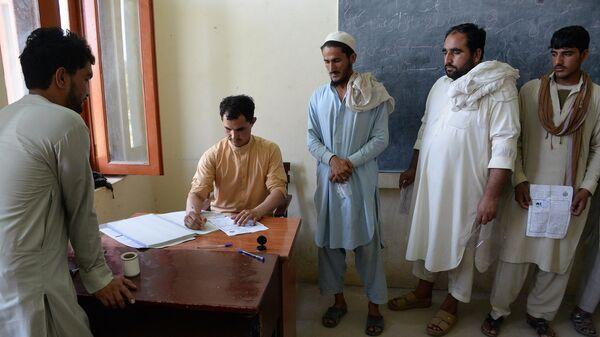 Афганские мужчины регистрируются для участия в выборах