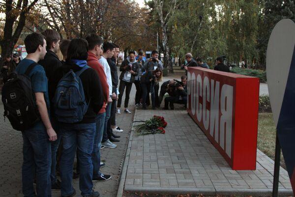 Цветы возле стелы Россия в сквере Первомайский в Донецке в знак траура по погибшим при взрыве в колледже в Керчи