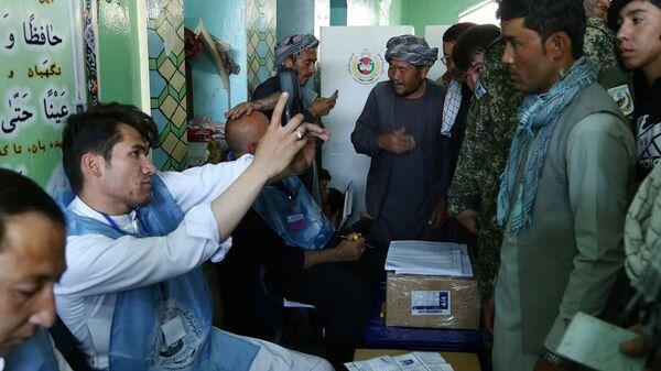 Мужчины во время регистрации перед голосованием на одном из избирательных участков Кабула. 20 октября 2018