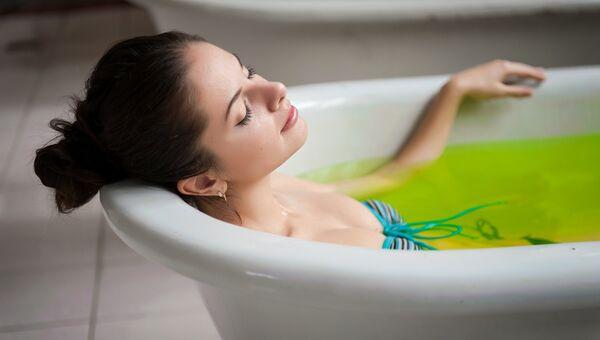 Женщина принимает ванну с зеленой водой