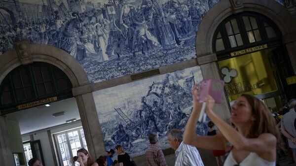 Девушка фотографирует изразцы в вестибюле станции Сан-Бенту в Порту, Португалия