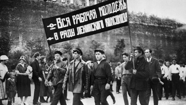Колонна комсомольцев с лозунгом Вся рабочая молодежь - в ряды Ленинского комсомола во время демонстрации на Красной площади