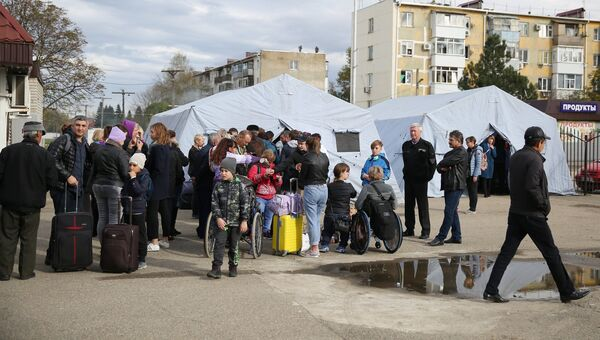 Пассажиры у полевого лагеря, развернутого добровольцами для организации питания пассажиров поездов, задержанных в Краснодарском крае из-за наводнения